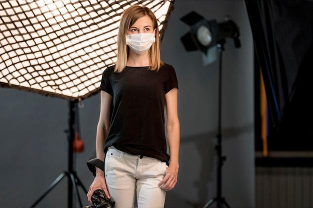 Mujer con máscara médica en un estudio.