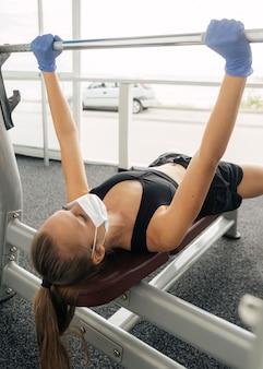 Mujer con máscara médica y guantes trabajando en el gimnasio