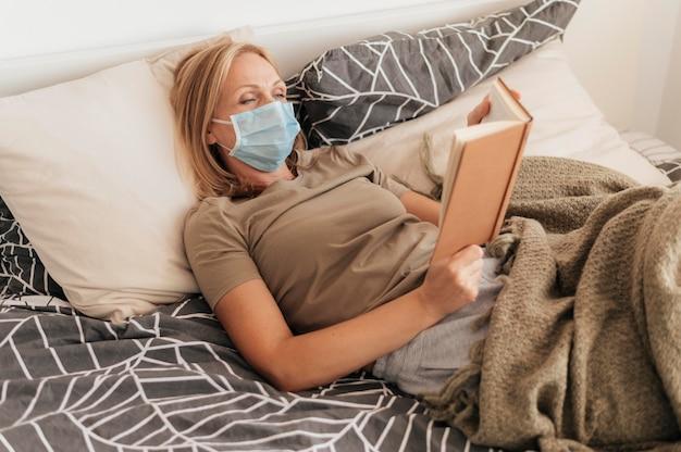 Mujer con máscara médica leyendo en cuarentena en casa