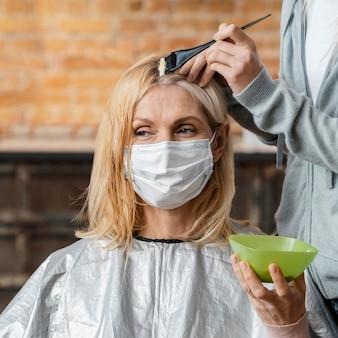 Mujer con máscara médica obteniendo su cabello teñido por peluquero en casa