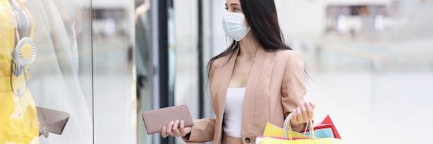 Mujer en máscara médica protectora mira vitrina de ropa en el centro comercial