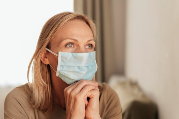 Mujer con máscara médica reflejando en casa durante la cuarentena