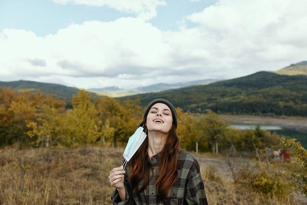 Mujer con una máscara médica respirando aire fresco en la naturaleza