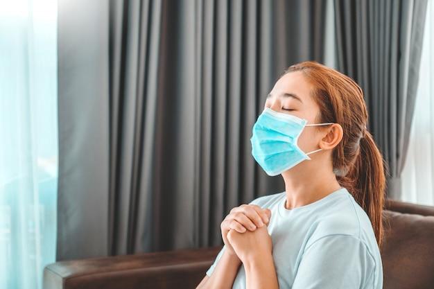 Mujer en máscara médica rezando en la mañana