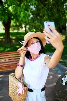 Mujer con máscara médica rosa en el parque toma selfie por teléfono móvil, la mujer con protección respiratoria está al aire libre mientras habla y tiene video chat por cámara web en el teléfono inteligente