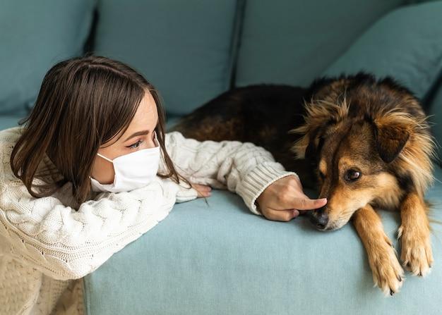 Mujer con máscara médica sentada junto a su perro durante la pandemia en casa
