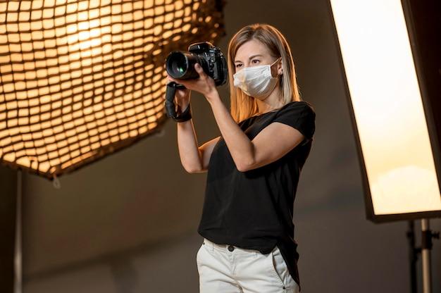 Mujer con máscara médica y tomar fotos