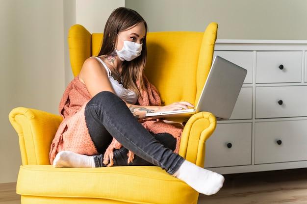 Mujer con máscara médica trabajando en una computadora portátil desde un sillón durante la pandemia