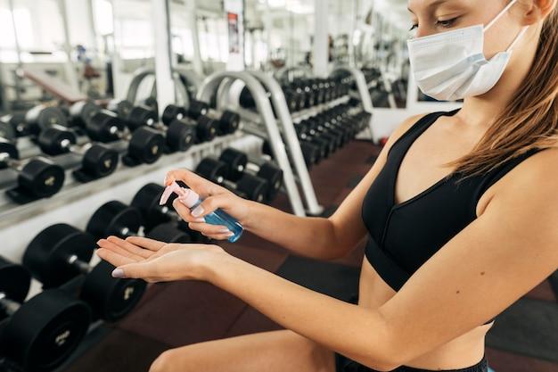 Mujer con máscara médica trabajando en el gimnasio y usando desinfectante para manos