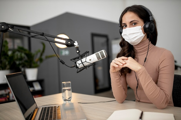 Mujer con máscara médica transmitiendo en radio con micrófono
