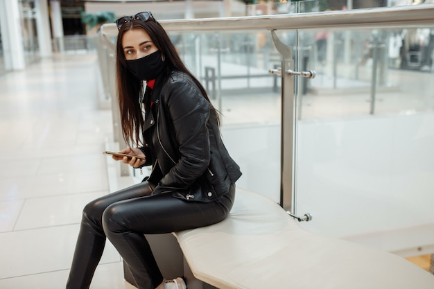 Mujer con máscara negra médica y teléfono móvil en un centro comercial. pandemia de coronavirus. una mujer con una máscara está de pie en un centro comercial. una mujer con una máscara protectora está de compras en el centro comercial