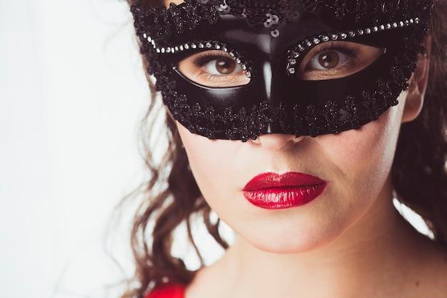 Mujer en máscara negra mirando a cámara
