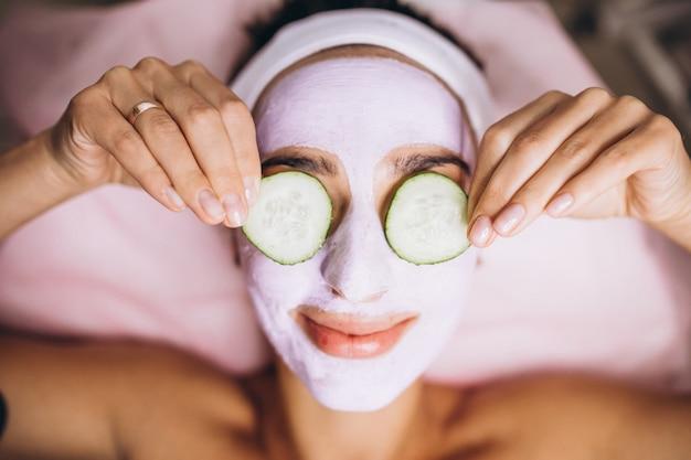 Mujer con máscara y pepino en los ojos