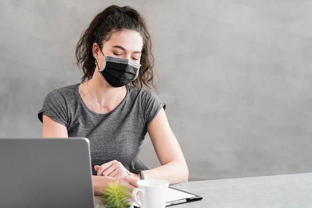 Mujer con máscara de protección en la oficina de negocios