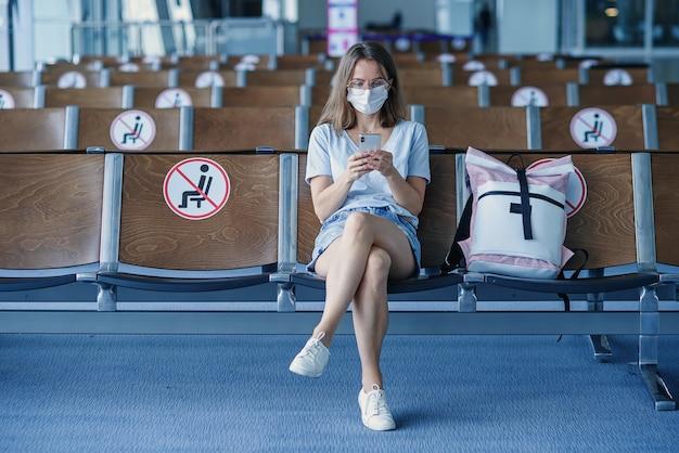 Mujer con máscara protectora esperando el avión en el aeropuerto hermosa chica usa teléfono móvil en