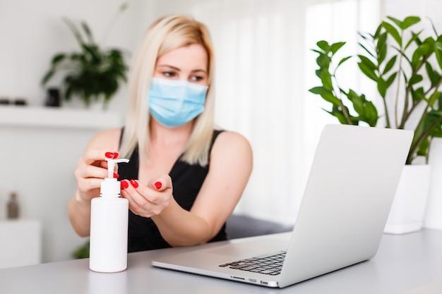 Mujer en máscara protectora médica con un gel antiséptico antibacteriano para desinfección de manos. prevención de la protección de la salud durante el brote del virus de la gripe y la epidemia de coronavirus