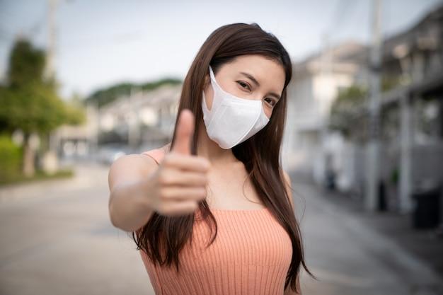 Mujer con máscara protectora, mostrando los pulgares para arriba.