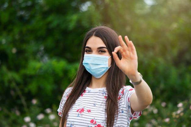 Mujer con máscara protectora y mostrando signo ok.