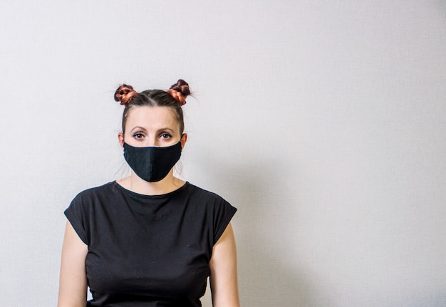 Mujer con una máscara protectora y un peinado interesante sobre una luz