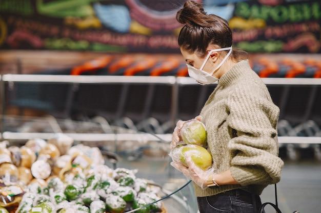 Mujer en una máscara protectora en un supermercado