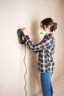 Mujer con máscara protectora trabajando con lijadora eléctrica para alisar la superficie de la pared de yeso, concepto de renovación de la habitación