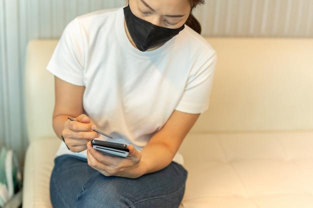 Mujer con máscara protectora trabajando en teléfonos inteligentes con lápiz digital.