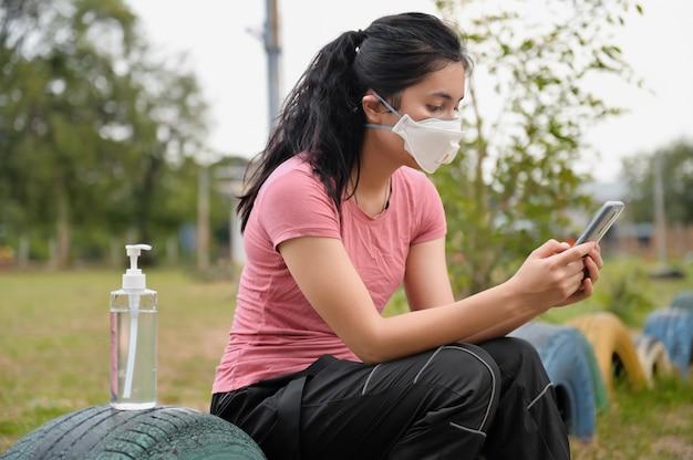 Mujer con máscara para proteger el virus corona covid19 para usar el móvil. concepto de salud