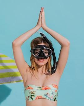 Mujer en la máscara que bucea que mira la cámara