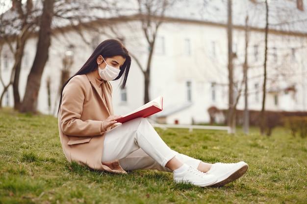 Mujer con una máscara sentada en un pasto