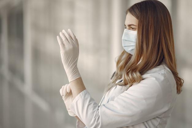 Mujer en una máscara y uniforme se pone guantes