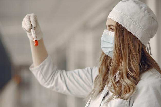 Mujer en una máscara y uniforme sosteniendo un tubo en sus manos