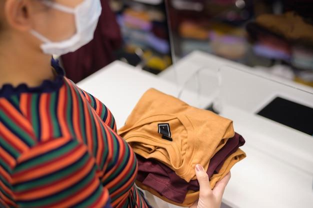 Mujer con mascarilla es comprar ropa en el centro comercial