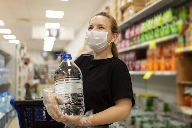 Mujer con mascarilla y guantes comprando en el supermercado, sonriendo, sosteniendo una botella de agua. compras de pánico durante la pandemia de coronavirus covid-19 compra económica en una tienda de suministros.
