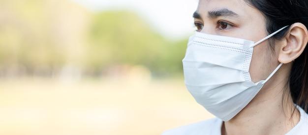 Mujer con mascarilla médica protectora para prevenir el coronavirus o la enfermedad por el virus de la corona (covid-19).