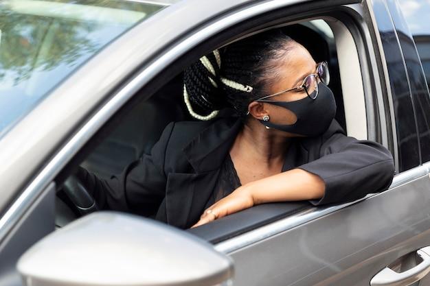 Mujer con mascarilla mirando hacia atrás mientras conduce su coche
