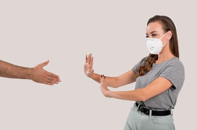 Mujer con mascarilla negándose apretón de manos