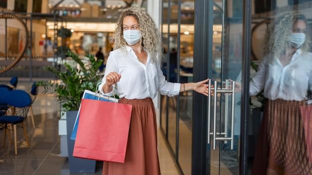Mujer, con, mascarilla, proceso de llevar, bolsas de compras