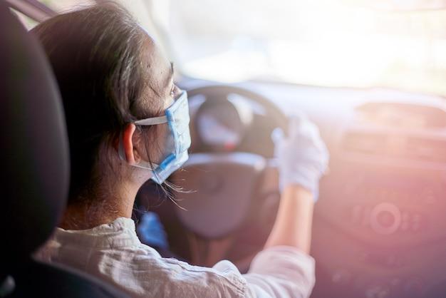 Mujer en mascarilla quirúrgica y guantes conduciendo coche