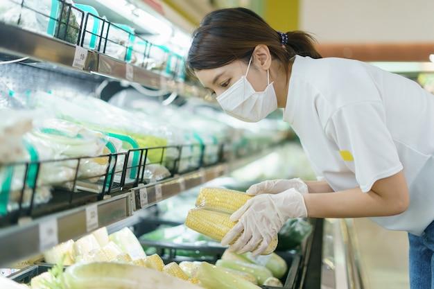 Mujer con mascarilla quirúrgica y guantes, elegir maíz en el supermercado después de la pandemia de coronavirus.