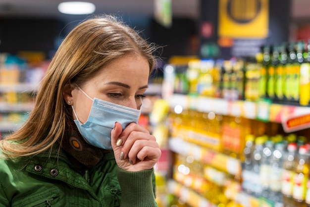 Mujer con mascarilla quirúrgica en tienda y tos