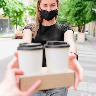 Mujer con mascarilla recibiendo bebidas calientes
