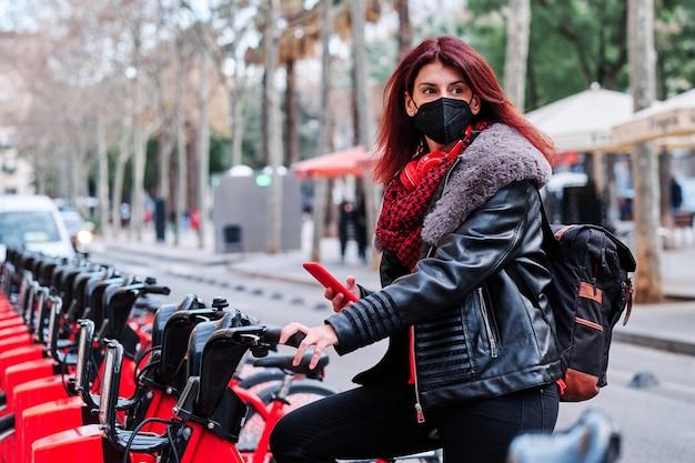 Mujer con mascarilla y usando su teléfono móvil mientras toma una bicicleta en un estacionamiento público de alquiler de bicicletas en la ciudad. nuevo concepto de estilo de vida normal.