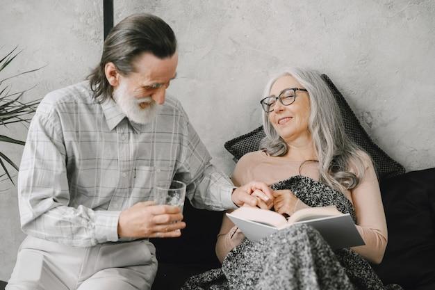 Mujer mayor acostada en la cama y tomando pastillas con su marido cariñoso. enfermedad, cuarentena.