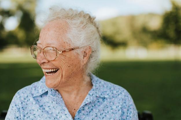 Mujer mayor alegre que se sienta en el parque