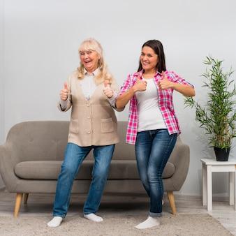 Mujer mayor alegre y su hija joven que muestran el pulgar encima de la muestra