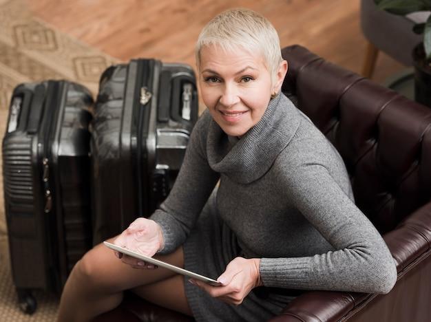 Mujer mayor de alto ángulo que sostiene una tableta