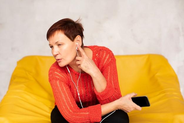 Mujer mayor de alto ángulo en el sofá escuchando música