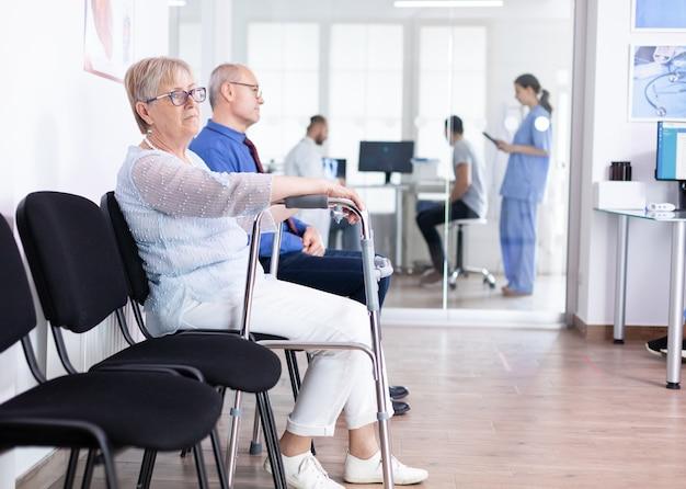Mujer mayor con andador en la sala de espera del hospital para tratamiento de rehabilitación