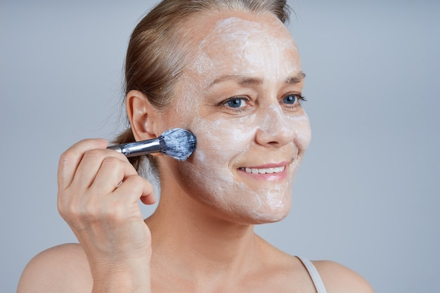 La mujer mayor se aplica una mascarilla cosmética a su rostro con un cepillo. cuidado de la piel facial en la vejez.