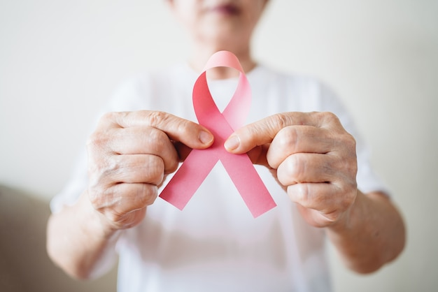 Mujer mayor apoya el día del cáncer de mama sosteniendo una cinta rosa
